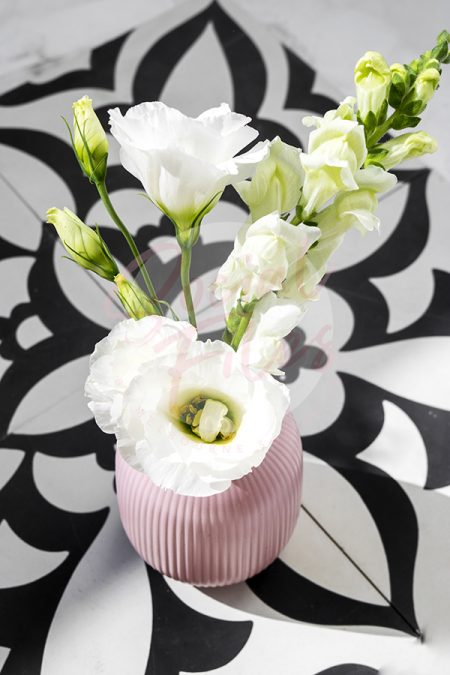 White flowers in pink vase, sitting on black and white tiles