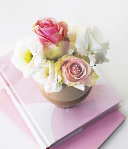 Pink and white flowers in small clay vase on pink notebooks