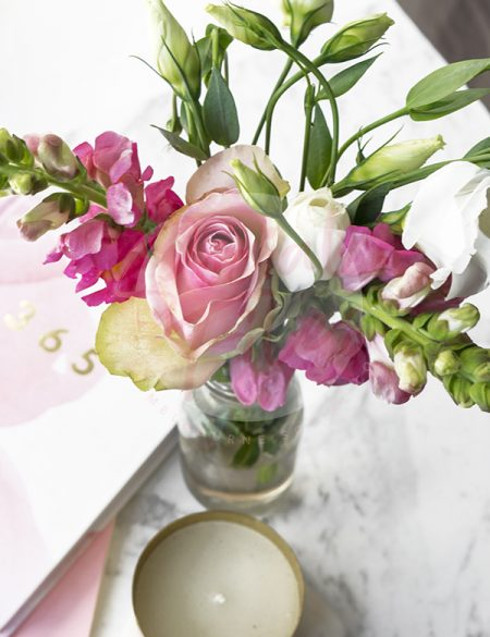 Mixed pink flowers in a small glass vase on marble, with pink diary