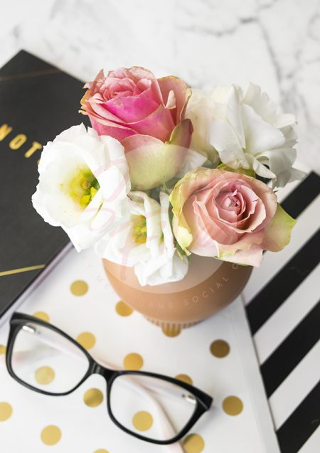 Mixed pink and white flowers in small clay vase, sitting on mixed stationery
