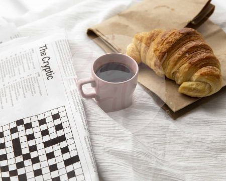 Coffee in pink espresso cup, on white background with croissant and crossword - watermarked image