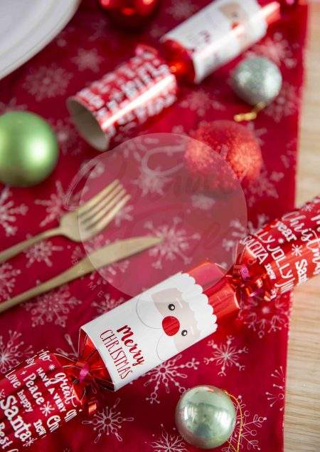 Christmas cracker with gold cutlery and decorations on red tablecloth. - watermarked image