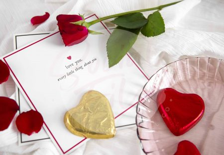 Valentine's Day Flatlay with Greeting Card, Red Rose & Heart Chocolates on White Fabric.