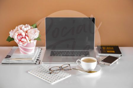 Laptop, diary, iphone, glasses, coffee and flowers on white desk with orange background. (watermarked)