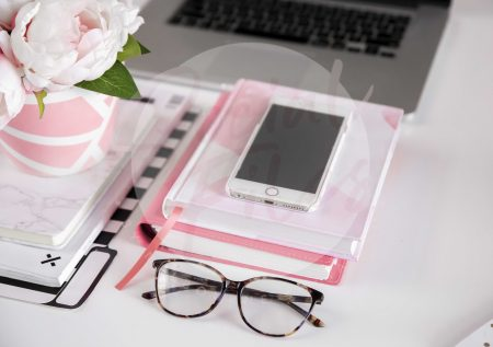Iphone, Laptop, diaries, glasses and pink flowers on white desk flatlay. (watermarked)