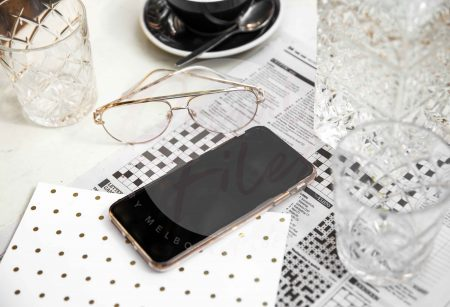 iPhone on marble table with newspaper, coffee and glasses (watermarked)