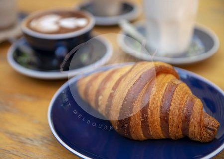 Croissant on wooden table with coffee in background (watermarked)