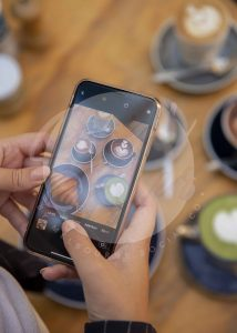 Woman taking photo on iphone of coffees and croissant, portrait (watermarked)