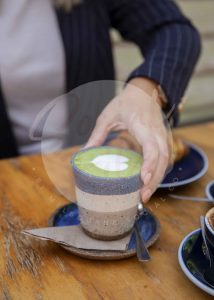 Woman's hand holding matcha latte with croissant on wooden table (watermarked)