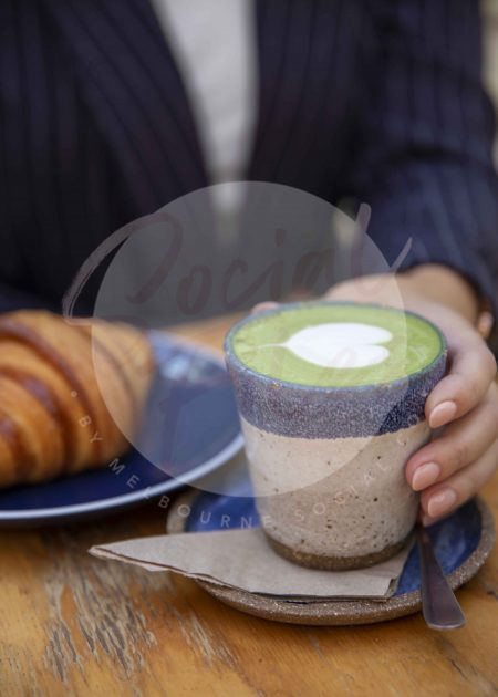 Woman's hand holding matcha latte with croissant on wooden table 02 (watermarked)