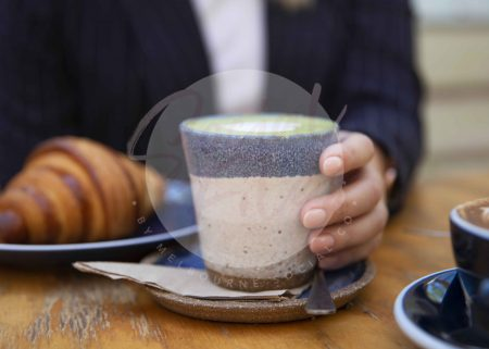 Woman's hand holding matcha latte with croissant on wooden table 03 (watermarked)