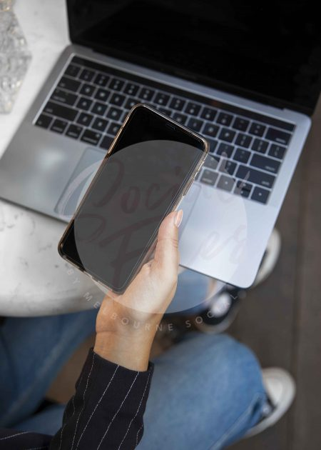 Woman's hand holding iPhone in front of laptop on marble table with water glass, portrait. (watermarked)